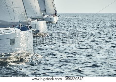 Sailboats Compete In A Sailing Regatta At Sunset, Sailing Race, Reflection Of Sails On Water, White