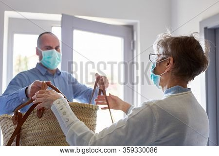 Groceries delivery to senior citizens with face mask in home quarantine for Covid-19 coronavirus