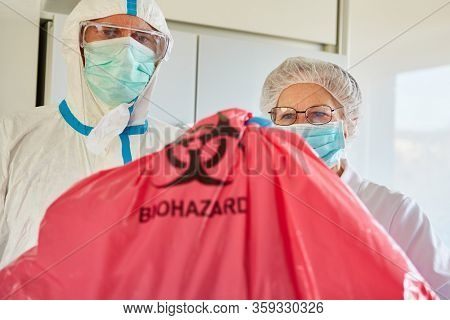 Cleaners dispose of infectious waste from Covid-19 patients in clinic during coronavirus epidemic