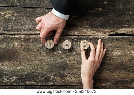 Gender Equality Conceptual Image - Male And Female Hand Placing Wooden Cut Circles With Gender Symbo