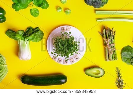 Top View Healthy Raw Vegetables On Yellow Background, White Plate With Sprouts And Go Vegan Message