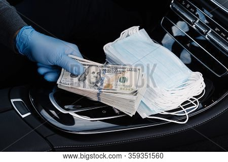 Virus Concept. Hand In Rubber Gloves Holds Stack Of Dollar Banknotes, Earns Money As Sells Medical M