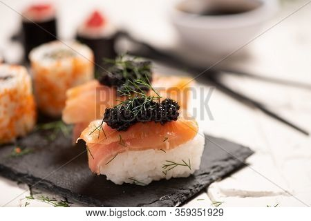 Salmon Sushi And Sushi Rolls, Bowl With Soy Sauce And Chopsticks, And Dollop Of Wasabi.