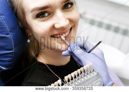 Dentist Checking On Female Patient Teeth Color, Using Tooth Enamel Scale, Dental Office Interior. Th