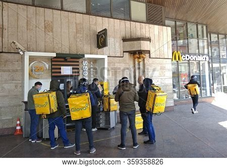 Kyiv, Ukraine - April 3, 2020: Couriers Of Glovo Delivery Service Waiting In A Line At Mcdonalds Exp