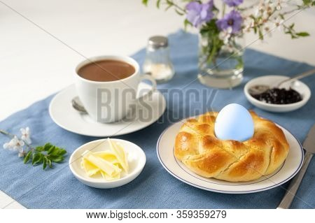 Plaited Bread Nest With An Easter Egg, Coffee, Butter, Jam And Flowers On A Blue Napkin And A White