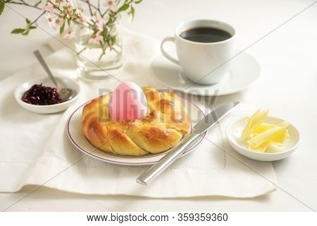 Easter Breakfast For One, Plaited Yeast Bread Nest With A Pink Egg, Coffee, Butter And Jam On A Whit