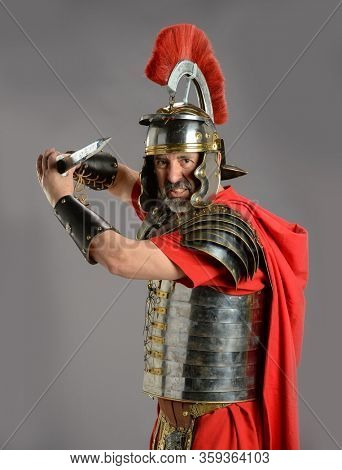 Roman Soldier holding a sword isolated on a gray background