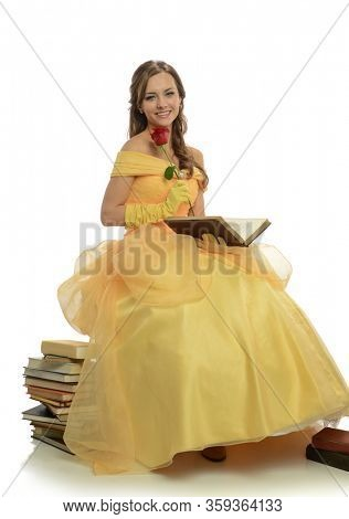 Young beautiful woman wearing a yellow princess gown sitting on top of a pile of books