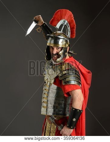 Roman soldier ready to strike with a sword isolated on a gray background