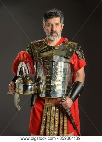 Roman soldier holding his helmet and gripping his sword on a dark background