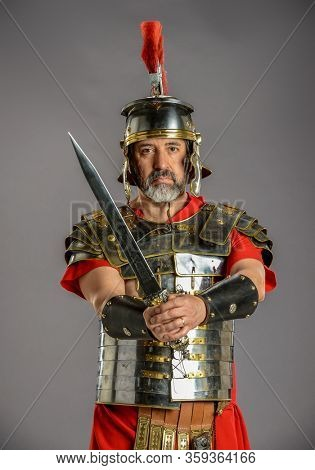 Roman soldier holding a sharp sword isolated on a gray background