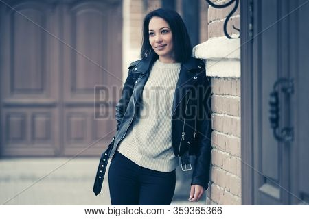 Young fashion woman on city street Stylish female model in black leather jacket and light gray pullover