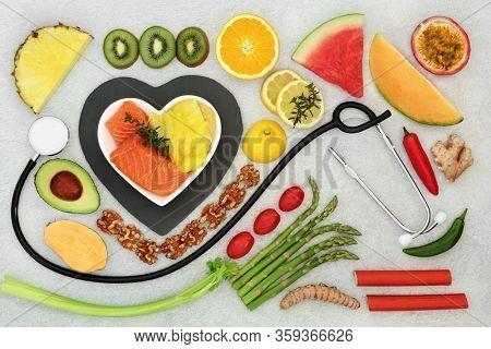 Health food for a healthy heart & cardiovascular system with stethoscope, fruit, vegetables, seafood,  herbs, spice &  nuts. High in omega 3, antioxidants, protein, anthocyanins & fibre with a low GI.