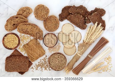Low glycemic food for diabetics with bread, pasta, crackers and noodles, high in minerals, dietary fibre, vitamins, antioxidants & smart carbs. Below 55 on the GI index. Flat lay on marble.