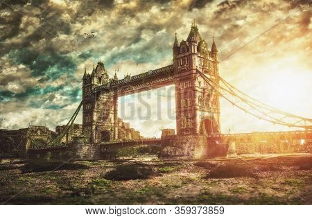Dramatic dark atmospheric fine art view of a deserted Tower Bridge London with overgrown weeds in foreground and fiery sky in a concept of an apocalypse because of pandemic, fire or climatic change