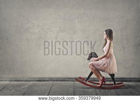 Pretty girl sitting on a rocking horse.