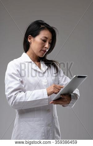 Dedicated Asian Nurse Or Doctor Checking Patient Notes On A Clipboard In Her White Lab Coat Over A G