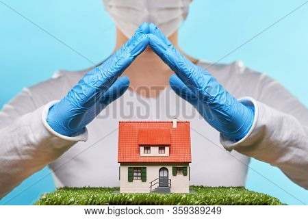 Woman In Medical Gloves And Mask Holds Hands Over A House. Concept Of Home Stay, Quarantine, Securit