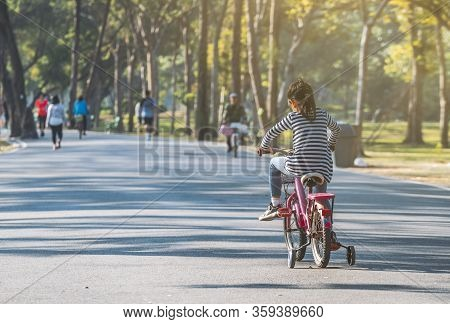 Activity Morning In Public Park Thailand, View Behind Asian Child Girl Practicing Biking Bicycle Wit