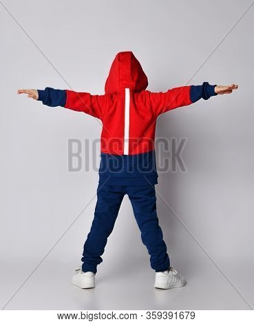 Full Growth Portrait Of Frolic Laughing Blond Kid Boy In Red And Blue Sport Suit Standing Back To Us