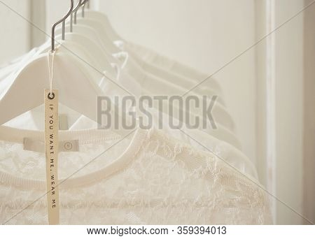 White Female Clothes Collection On Wooden Hangers