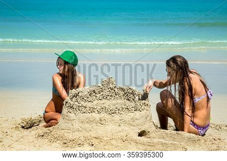 Two Young Women Friends Build A Large Sand Castle On The Beach