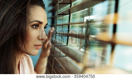 Young woman looking through the window