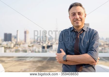 Happy Mature Handsome Businessman Smiling With Arms Crossed In The City