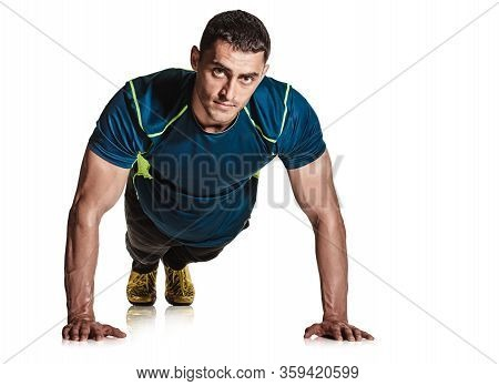 Portrait Of Fit Strong Man In Sportswear Doing Push-up Exercise On White Background