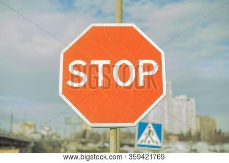 Stop Sign - Red With White Text With Blue Sky, Clouds, Buidings And Pedestrian Crossing Sign In Back