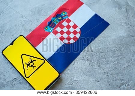 Epidemiological Situation In The Country Croatia. Flag And Smartphone With News And A Biohazard Symb
