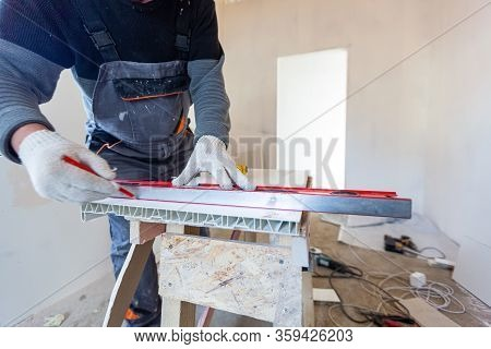 Worker Is Measuring The Plastic Detail Before It Cutting In Apartment That Is Under Construction, Re