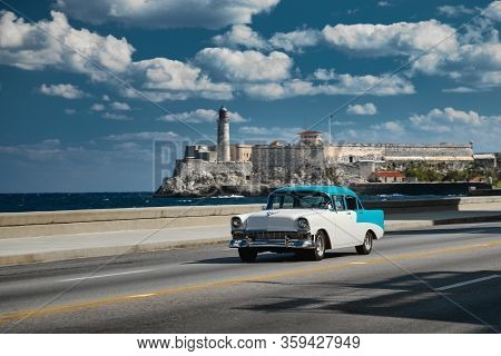 Havana, Cuba - March 22, 2019: Retro Car On The Embankment. El Morro Castle And Lighthouse On Backgr
