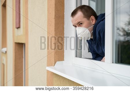 Caucasian Adult Man In Protective Mask Looks Out Of An Open Window. Stay Home Concept. Quarantine An