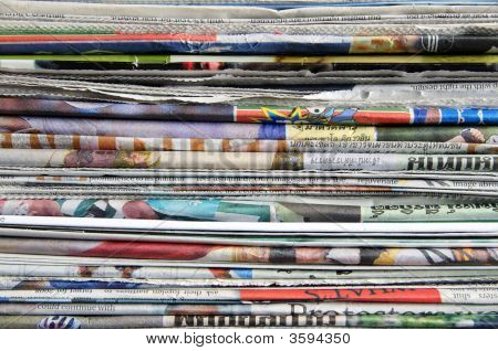 A pile of old mixed Thai and English newspapers poster