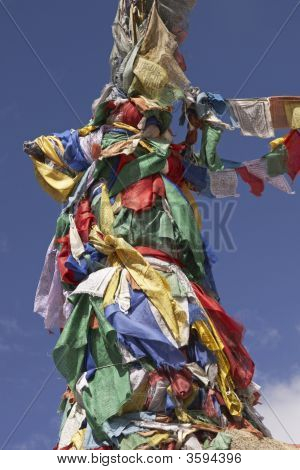 Buddhist prayer flags mark the summit of a mountain in Leh Ladakh India mountaintop poster