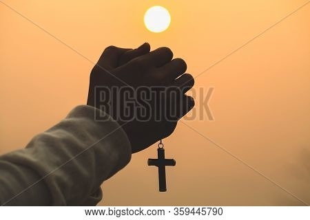 Both Hands Grasped The Cross To Pray To God. While The Sun Is Setting Or Rising Christian Religious