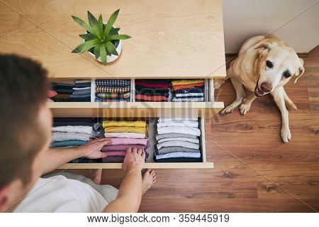 Organizing And Cleaning Home. Man Preparing Orderly Folded T-shirts In Drawer.