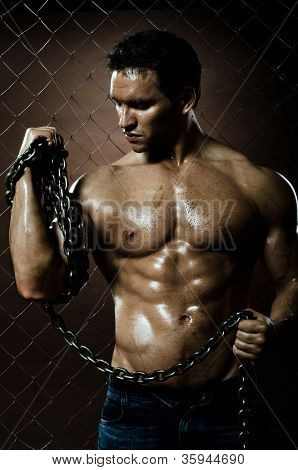 poster of the beauty muscular worker man with big chain in hands on netting fence background
