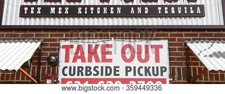 Babylon, New York, Usa - 1 April 2020: Take Out Only With Curbside Pickup Sign Posted On A Brick Wal