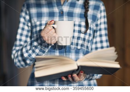 Woman holding cup of hot drink and a book, story reading concept