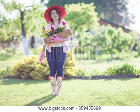 Woman wearing hat and wellies holding pot with flowers in the garden