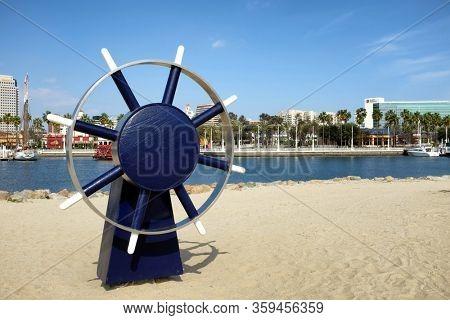 LONG BEACH, CALIFORNIA - 21 FEB 2015: Ships Helm Wheel at Shoreline Aquatic Park with Rainbow Harbor and city skyline in the background.
