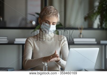 30s Businesswoman In Protective Medical Facemask Disinfecting Hands.