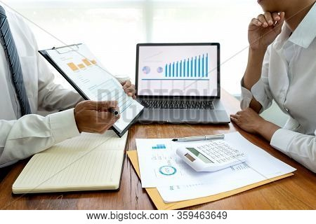 Business Team In Casual Style Have Small Meeting In The Office Talk About  Analyses Chart Graph Mark