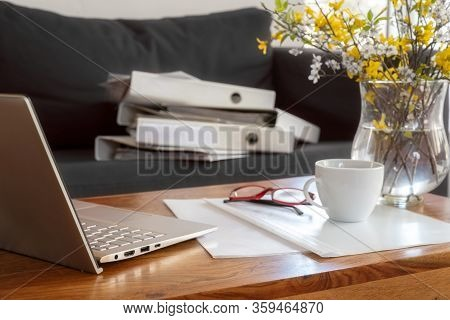 Laptop, Documents And Ring Binders On A Wooden Coffe Table And The Couch Behind, Working In A Tempor