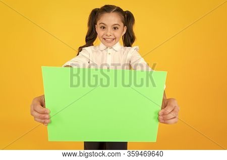 Being Given A Home Work. Little Child Holding Empty Sheet For Examination Work On Yellow Background.