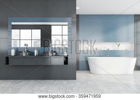 Interior Of Spacious Bathroom With Grey Tile And Blue Walls, Concrete Floor, Comfortable Bathtub And