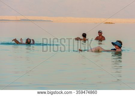 People Enjoying The Dead Sea At Golden Hour